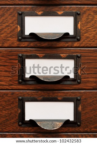 Vertical stack of three small, old oak flat file drawers with white empty tags in tarnished brass label holders. - stock photo