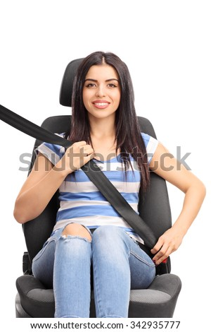 Vertical studio shot of a young woman sitting on a car seat fastened with a seatbelt isolated on white background - stock photo
