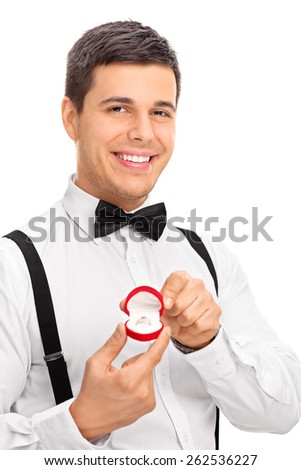 Vertical studio shot of an elegant young man holding an engagement ring, smiling and looking at the camera isolated on white background - stock photo