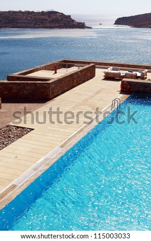 Vertical summer landscape with Mediterranean sea, pool and terrace in luxury resort (Greece) - stock photo