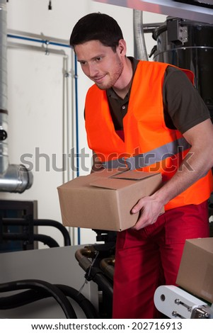Vertical view of a blue-collar worker holding box - stock photo
