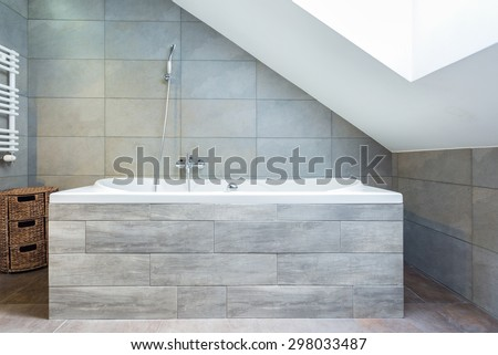 Vertical view of bathtub with wooden housing - stock photo
