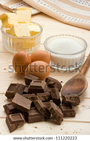 "Vertical view of chocolate ""Cake Ingredients"" on pine wood table. - stock photo"