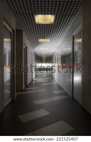 Vertical view of corridor in corporate building with glass walls - stock photo