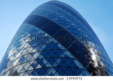 Vertical view of the Gherkin skyscraper with a blue sky background - stock photo