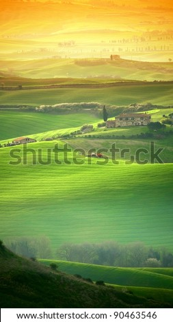 Vertical view of Tuscany landscape shot with orange gradual filter. Morning sunlight shines over the hilly landscape with thin haze. - stock photo