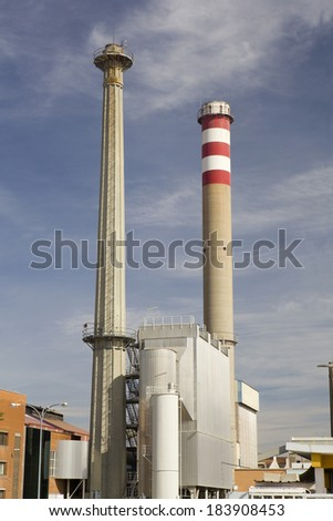 Vertical view of two tall smokestacks in a modern factory. Two smokestacks - stock photo