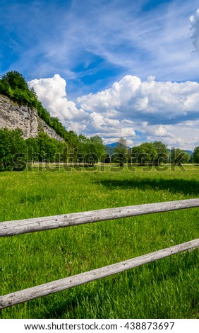 Vertical view to the old wooden fence surrounding natural green Alpine meadow with snowy mountain peaks under a beautiful feather clouds on a bright blue sky in the background, Salzburg, Austria - stock photo