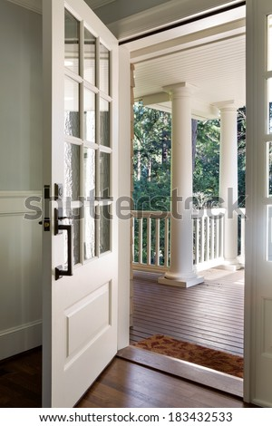 Of an open wooden front door from the interior of an upscale home
