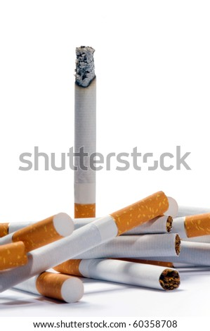vertically standing cigarette and a few cigarettes lying on a white background - stock photo