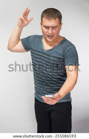 very angry businessman is throwing away his mobile phone - stock photo