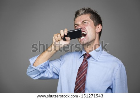 very angry businessman si biting his mobile phone - stock photo