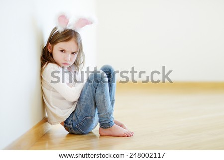 Very angry little girl wearing bunny ears sitting on a floor at home - stock photo
