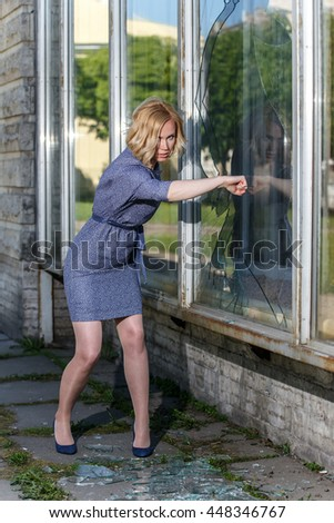 Very angry woman braking glass window by her fist - stock photo