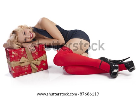very attractive and sexy blond pin up with red christmas stocking and a big present box laying on the floor - stock photo