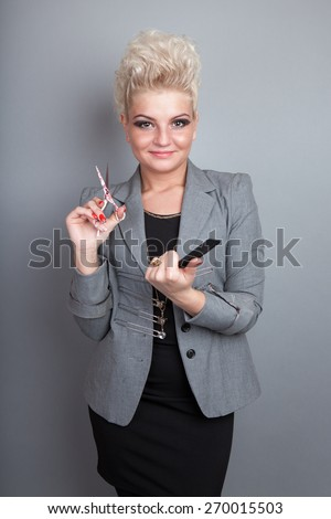 Very attractive and stylish professional hairdresser woman with scissors and comb. With stylish blonde hair. In elegant outfit on grey background - stock photo