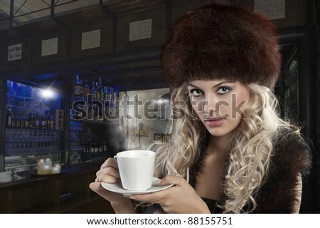 very attractive blond curly woman in elegant dress with fur stole and hat drinking a cup of tea - stock photo