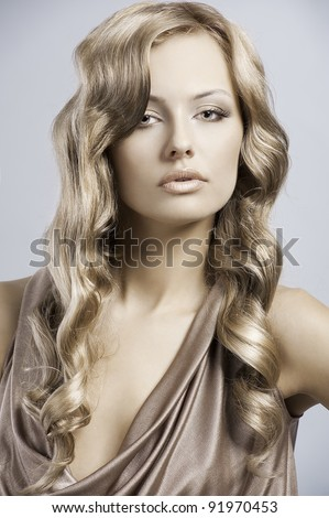 very beautiful and attractive young blond lady in elegant silk dress and with old fashion hair style - stock photo