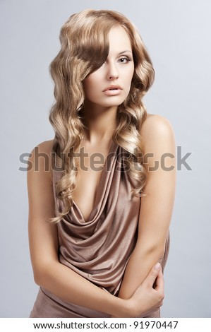 very beautiful and attractive young woman with long blonde hair  in elegant silk dress and with old fashion hair style - stock photo