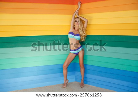 Very beautiful blonde the woman with long legs is standing in high heels and the fantastically colour swimsuit against the colourful background made of wood - stock photo