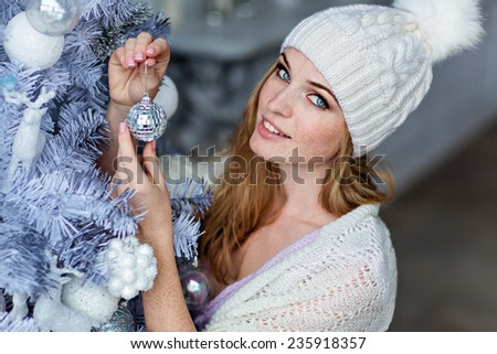 Very beautiful girl with blue eyes in a white hat costs about silver Christmas tree and smiling, close up - stock photo