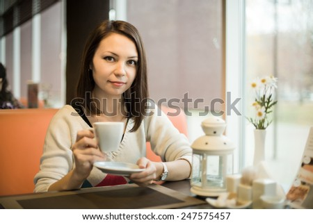 Very beautiful, happy,  young woman, sit in  Cafe and drink coffee, horizontal portrait - stock photo