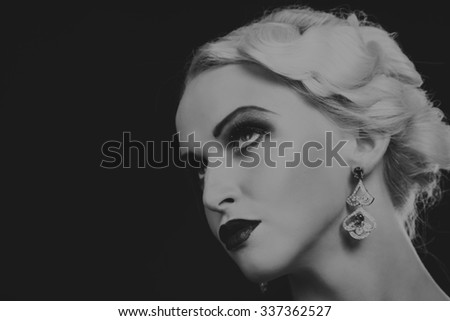 Very beautiful image of the model in vintage dress on a dark background. Portrait black and white photo blonde lady in the form of 20th years. Stylish jewelry. Professional makeup.  - stock photo