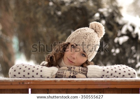 Very beautiful,pretty girl with hat,sweater,warm mittens,curly,brown hair in winter,snowbound forest look,you,curl up,put head on hands,put hands,turned,inclined head,tone,creative,beige,light,girl  - stock photo