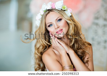 Very beautiful sensual girl with curly blond hair and a wreath of delicate spring flowers, close up - stock photo
