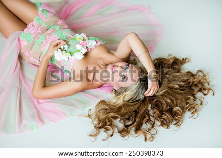 Very beautiful sexy sensual girl with curly blond hair and a wreath of delicate spring flowers, lying on white floor - stock photo