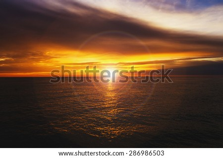 Very beautiful sunset at sea in yellow with a lens flare effect - stock photo