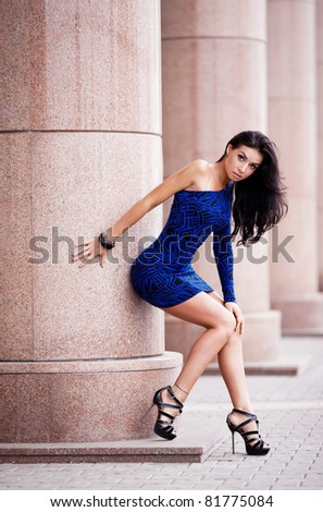 very beautiful young brunette woman wearing a mini dress in the street - stock photo