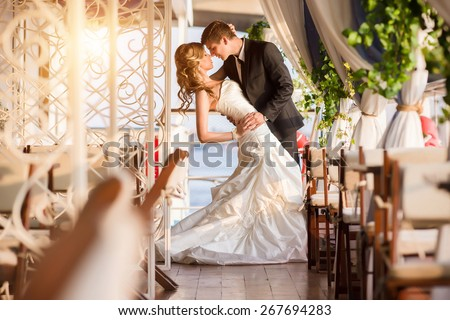 Very beautiful young couple posing after the wedding ceremony on the open terrace - stock photo