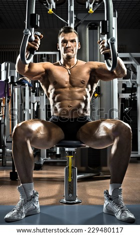 very brawny guy bodybuilder ,  execute exercise  on gym apparatus Butterfly Machine, in gym - stock photo