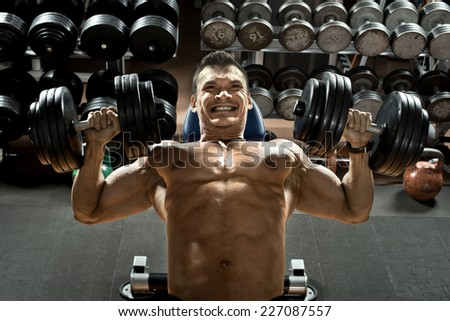 very brawny guy bodybuilder ,  execute exercise press of dumbbells on pectoral muscle, in gym - stock photo
