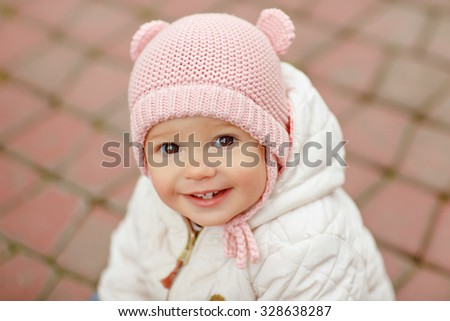 Very charming beautiful little girl with big brown eyes in a pink cap smiles in autumn, close-up - stock photo