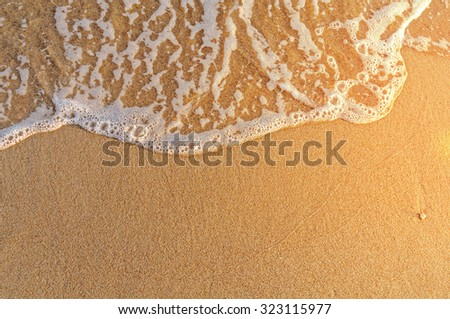 Very close sand beach and wave in Greece, burning sun - stock photo