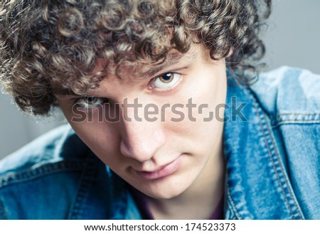Very closeup portrait of a young caucasian guy with curly hair - stock photo