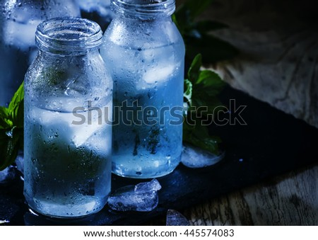 Very cold mineral water with ice in a misted glass bottles, dark background, selective focus - stock photo