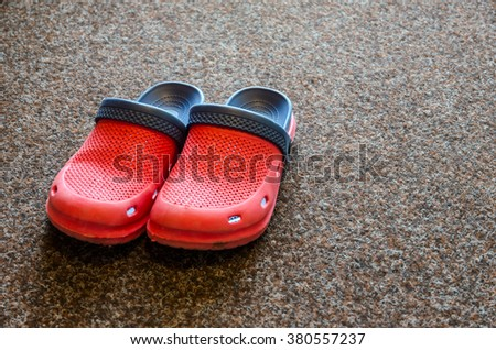 Very confortable red garden slippers on a carpet.  - stock photo