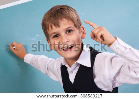 Very cute and positive student is smiling and writing on school blackboard - stock photo