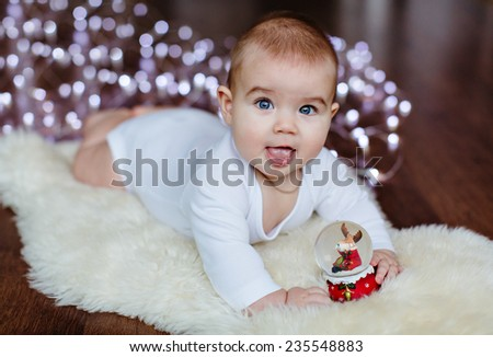 Very cute baby lying on the floor on the background lights near the Christmas ball and smiling - stock photo