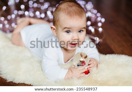 Very cute baby lying on the floor on the background of Christmas lights and holding a Christmas ball pens - stock photo