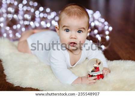 Very cute baby lying on the floor on the background of Christmas lights near the ball - stock photo