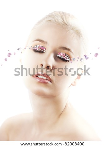 very cute blond young woman with hair style with some shining gem stone on her eyes as a creative make up - stock photo