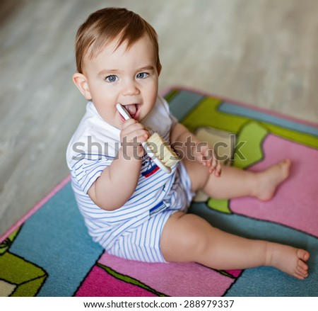 Very cute little blond boy chews on the brush for the hair, scratching his teeth, sitting on the colored carpet - stock photo
