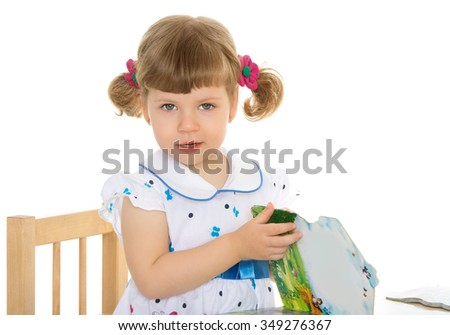 Very cute, little, blond girl with short bangs and little pigtails on her head in elegant white dress with polka dots. A girl sits at a table and leafing through a picture book . closeup - Isolated on - stock photo