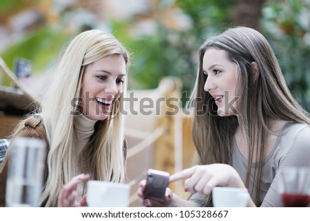 very cute smiling women drinking a coffee sitting inside in cafe restaurant - stock photo