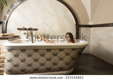 very cute woman sitting relaxed in a bathtub in elegant rustic bathroom in a luxury spa, smiling and looking in camera.  - stock photo