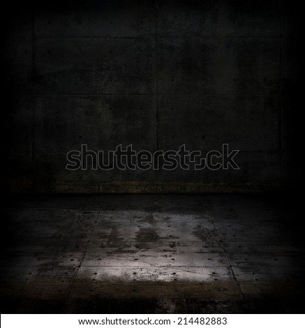 Very dark concrete or stone space with faint light on the floor.  - stock photo